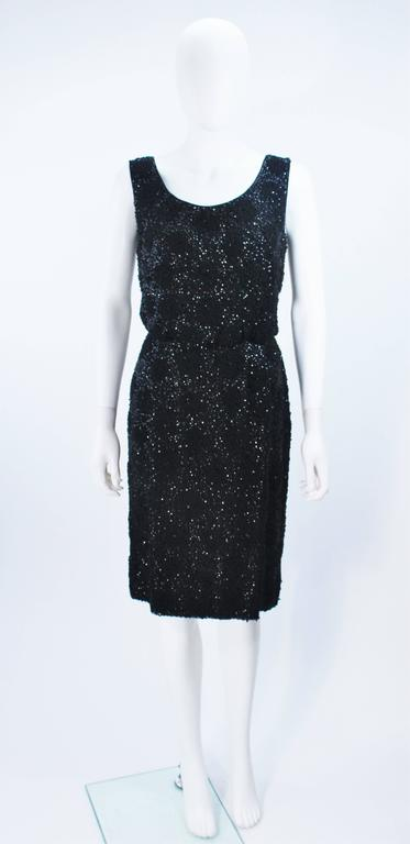This cocktail dress is composed of a black silk chiffon with floral patterned beading throughout. There is a center back zipper closure. In great vintage condition.     **Please cross-reference measurements for personal accuracy. Size in