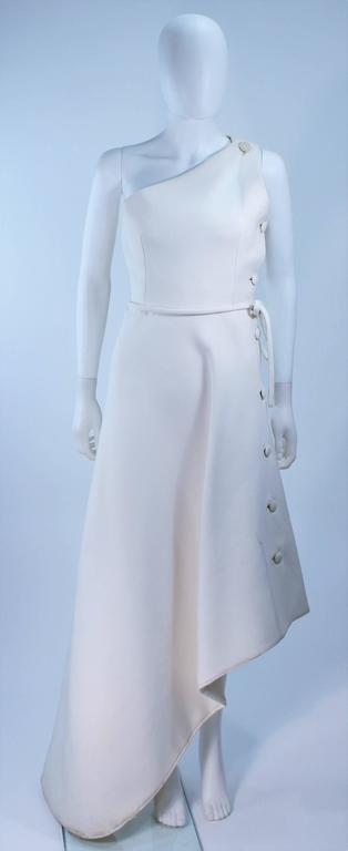 This Givenchy Haute Couture Gown is composed of a white wool and features an asymmetrical design with side button detail. In excellent vintage condition with some discoloration due to age.