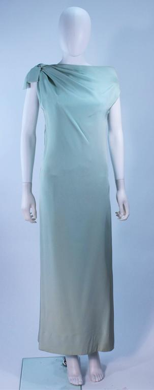This Christian Dior  gown is composed of an aqua crepe silk with as silk satin slip. Features an asymmetrical design with a side zipper. In excellent vintage condition, there are some signs of wear due to age. 