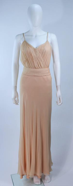 This Ceil Chapman gown is composed of a nude silk chiffon. Features a draped and gathered design, with interior boning. There is a center back zipper closure and belt. In great vintage condition. 