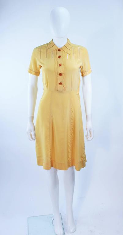 This dress is composed of a yellow hue silk. Features sheer lace inserts, front pockets, and center front buttons. In excellent vintage condition, some slight discoloration due to age.
