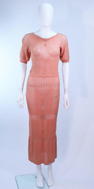 This gown is composed of a terracotta hue knit. Features a draped neckline and tea length. In excellent condition.