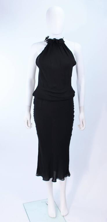 This Ungaro dress is composed of a bias cut black silk. Features ruffle halter neck and side snap closures. In excellent vintage condition.