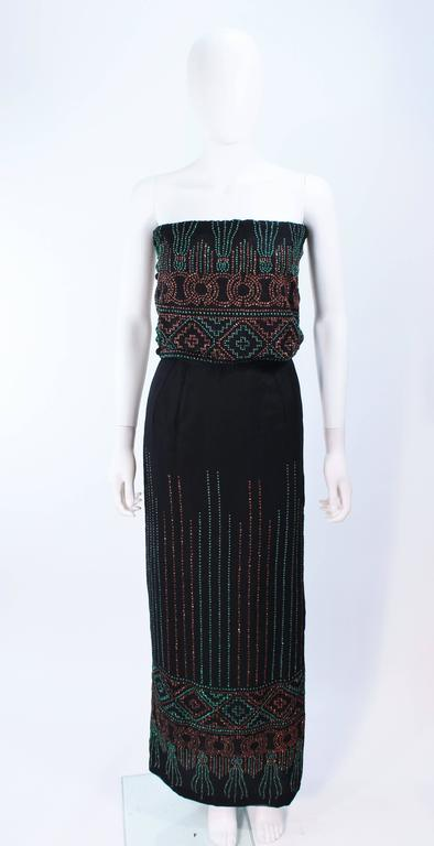 This ensemble is composed of black silk with sequin applique. Features pants, skirt, and tube top with elastic & button closures. Pants and skirt have zipper closures. In excellent vintage condition.