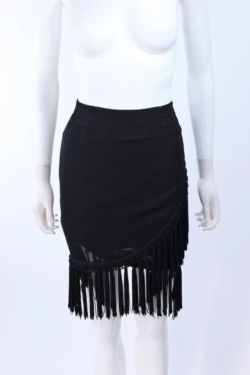 This Diane Frez design is composed of a black silk chiffon and features a tassel trim. Wrap style with elastic waist. In excellent vintage condition.