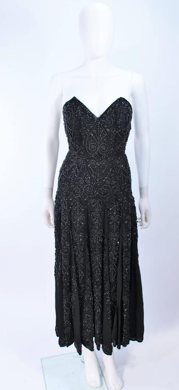 This Eavis & Brown design is composed of black velvet with chiffon godets and heavy beaded embellishment. There is a center back zipper closure, and interior waist belt and boned bustier. In excellent vintage condition.  **Please cross-reference