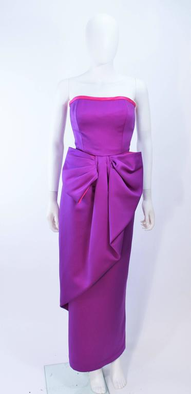 This Victor Costa gown is composed of a purple and magenta combination. Features a front draped bow at the waist. There is a center back zipper closure. In excellent vintage condition.