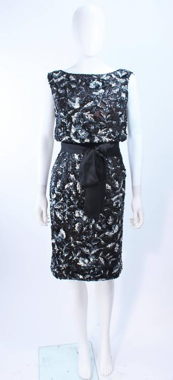 This vintage cocktail dress is composed of a silk chiffon with a sequin floral applique in silver and black hues. There is a side zipper closure with hook and eyes. In excellent vintage condition.
