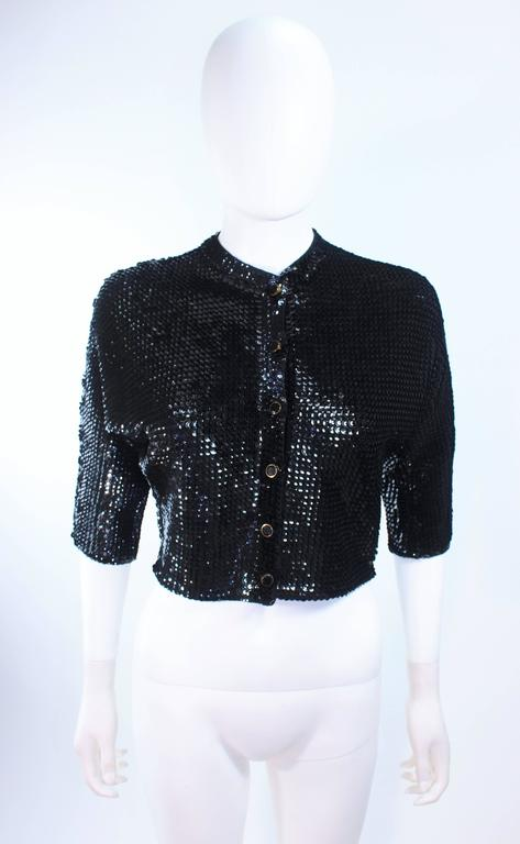 This vintage cardigan is composed of a black sequin wool. There are center front black and gold faceted buttons. In excellent vintage condition.  **Please cross-reference measurements for personal accuracy. Size in description box is an