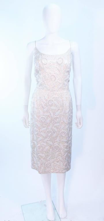 This Haute Couture International cocktail dress is composed of an off white silk with iridescent sequin applique in a floral motif. There is a center back zipper closure. In excellent vintage condition.  **Please cross-reference measurements for