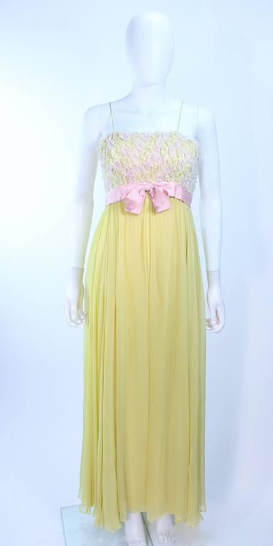 This Victoria Royal gown is composed of a yellow silk chiffon with pink floral applique and rhinestones. There is a center back zipper closure. In excellent vintage condition, one small mend on the skirt, barely visible.