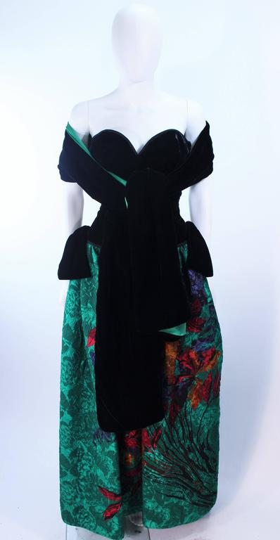 This Odicini Couture gown is composed of a black velvet bodice and green floral skirt. Comes with reversible velvet and silk wrap. There is a center back zipper closure. In excellent vintage condition.