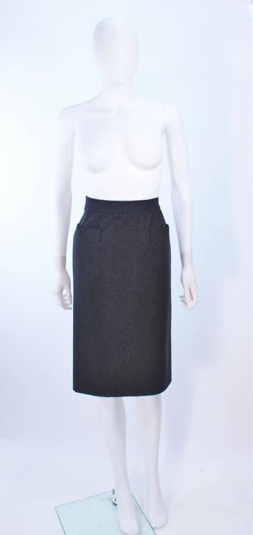 This Yves Saint Laurent skirt is composed of a charcoal wool. Features a pencil  silhouette with front pocket applique. There is a zipper closure. In excellent vintage condition.
