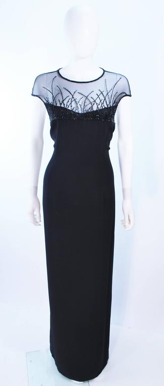 This Bob Mackie gown of a black crepe fabric with a beaded sheer mesh bodice. There is a center back zipper closure with train. In excellent vintage condition.