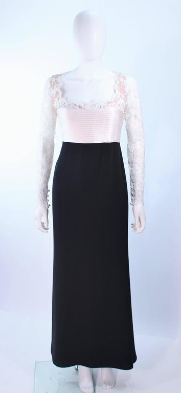 This Carolina Herrera design is composed of a white lace bodice, with top-stitched satin waist, and black skirt. There is a center back zipper with buttons. In excellent vintage condition.