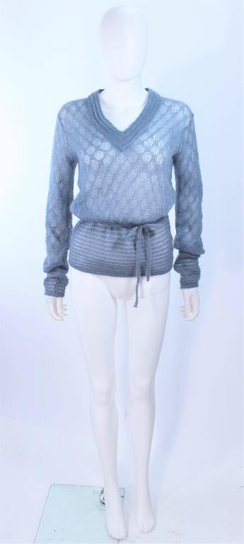 This Missoni design is composed of a sky blue wool with a semi sheer knit property. Features a v-neck with waist tie. In excellent vintage condition.  **Please cross-reference measurements for personal accuracy. Size in description box is an