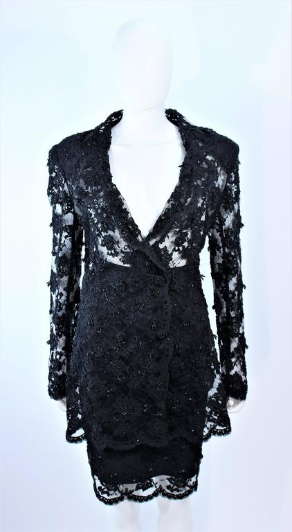 This Fetoun skirt suit is composed of beaded black lace. The jacket features a sheer design with center front snap closures The skirt has a classic pencil style with zipper closure. In excellent vintage condition.  **Please cross-reference