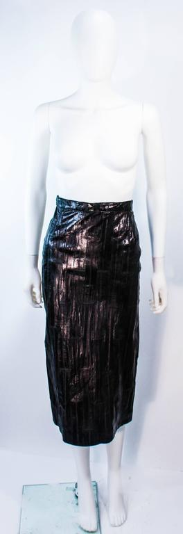 This Krizia design is composed of black eel with a shine finish. Features a midi length with zipper closure. In excellent vintage condition.  **Please cross-reference measurements for personal accuracy. Size in description box is an estimation.