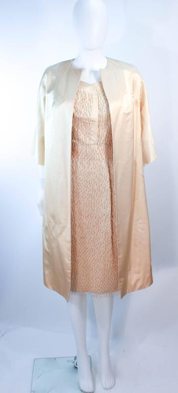 This vintage set is composed of a cream silk and features a cocktail dress with beaded fringe detailing throughout. The dress has a zipper closure. The jacket is a classic open style opera coat. In excellent vintage condition, some discoloration due