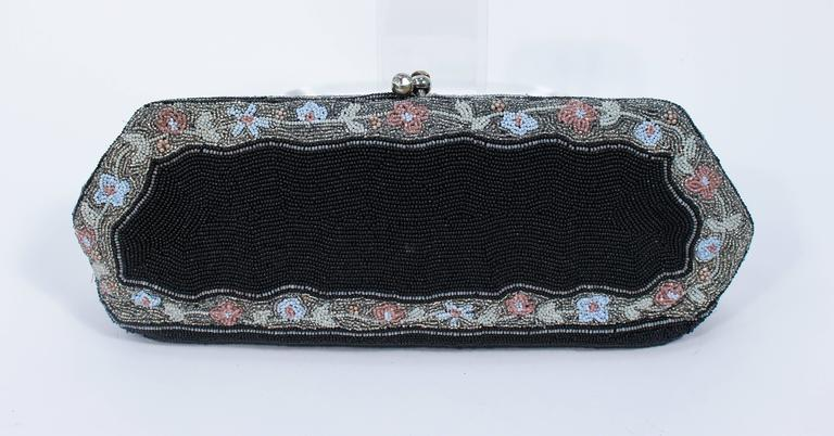 This purse hand beaded purse was manufactured in Belgium for Bergdorf. Features a stunning and immaculate hand beaded design with rhinestone detailing on the closure. There is an interior compartment with silk lining. In excellent vintage condition,