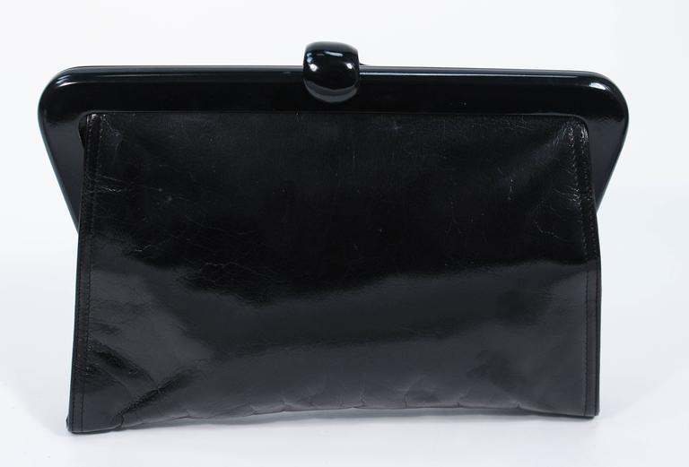 This Bottega Venta purse is composed of a polished black calfskin. Features a lever style clasp. There is an interior zipper compartment. Made in France. In excellent vintage condition, there is some marking on the back of the purse which maybe