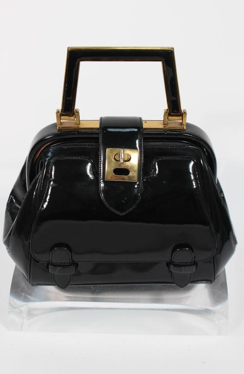 This Judith Leiber handbag is composed of a black patent leather with gold tone hardware. It is a very rare 1960's design featuring turn style closures with an exterior pocket. There are interior compartments with a silk lining. In excellent vintage
