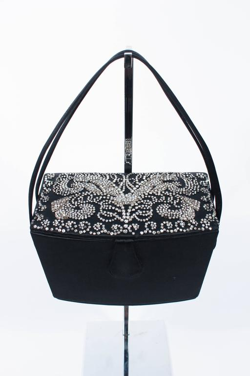 This vintage Josef purse is composed of a black silk satin. Features an intricate rhinestone rhinestone applique top. Comes with a rhinestone pen, wallet, and miniature mirror. There is an interior compartment with silk lining and mirrored interior