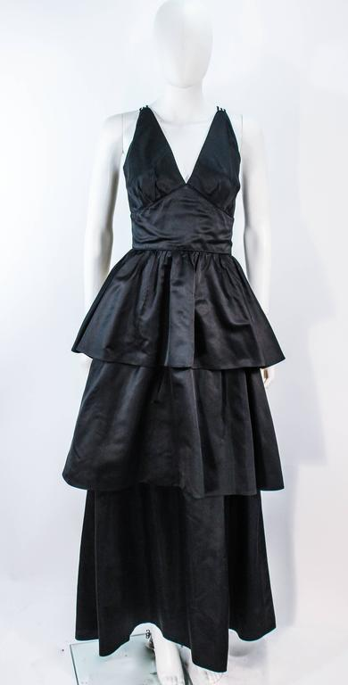 This Michael Novarese gown and jacket is composed of a black satin. The jacket has center front button closures. The gown has a multi strap design with center back zipper closure. In excellent condition.   **Please cross-reference measurements for