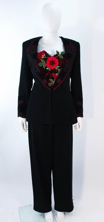 This Fe Zandi suit is composed of a black fabric with red lac/ eyelet accents. Features a stunning floral bustier with a center back zipper closure. The jacket has a lace trim collar with hook and eye closure. The pants have a side zipper closure.