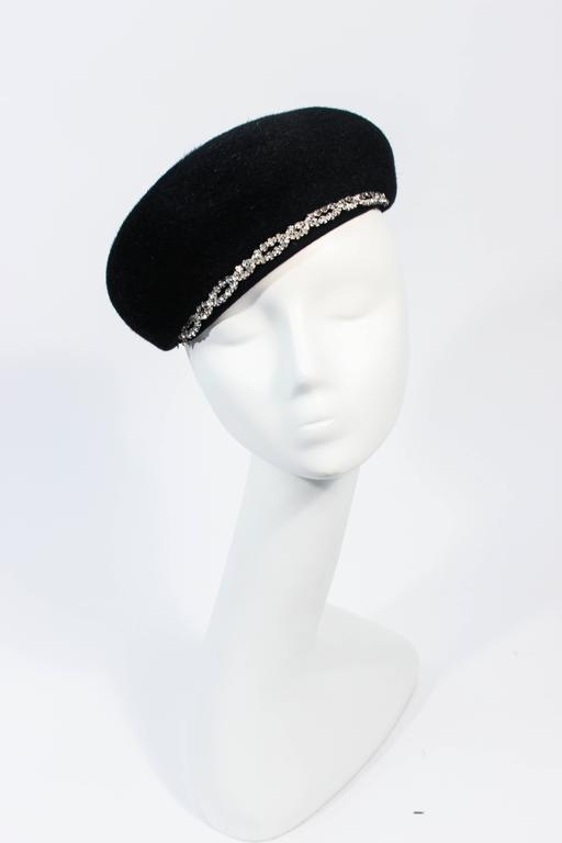 This Schiaparelli design is composed of a black fabric and features a rhinestone trim with two hat pins. Can be styled in a multitude of fashions, an amazing design. In excellent vintage condition.  **Please cross-reference measurements for personal