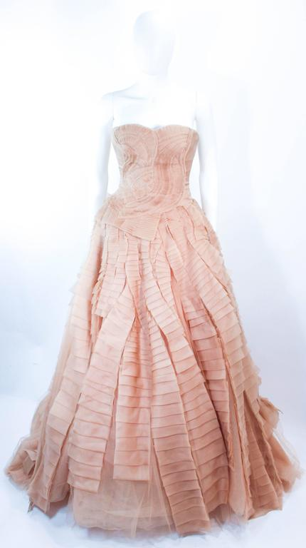 This Vera Wang wedding gown is composed of layers of nude organza and tulle. The bodice features a gathered detailing with a boned interior and center back zipper closure. In excellent pre-owned condition (there are a few faint spots due to