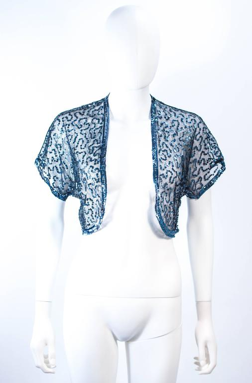This antique jacket is composed of a sheer black mesh with blue sequin applique. Features an open style. In excellent vintage condition.   **Please cross-reference measurements for personal accuracy. Size in description box is an estimation.