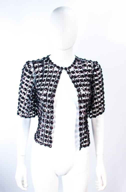 This antique jacket is composed of a sheer black mesh with a bronze brown sequin applique. There is a center front hook and eye closure. In excellent vintage condition.   **Please cross-reference measurements for personal accuracy. Size in