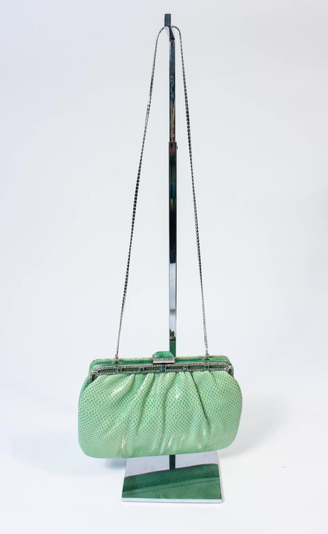 This  Judith Leiber vintage purse is composed of a mint lizard skin, Features a frame style with optional chain strap. There is an interior zipper compartment. In excellent vintage condition, there is slight color variation due to age, but appears