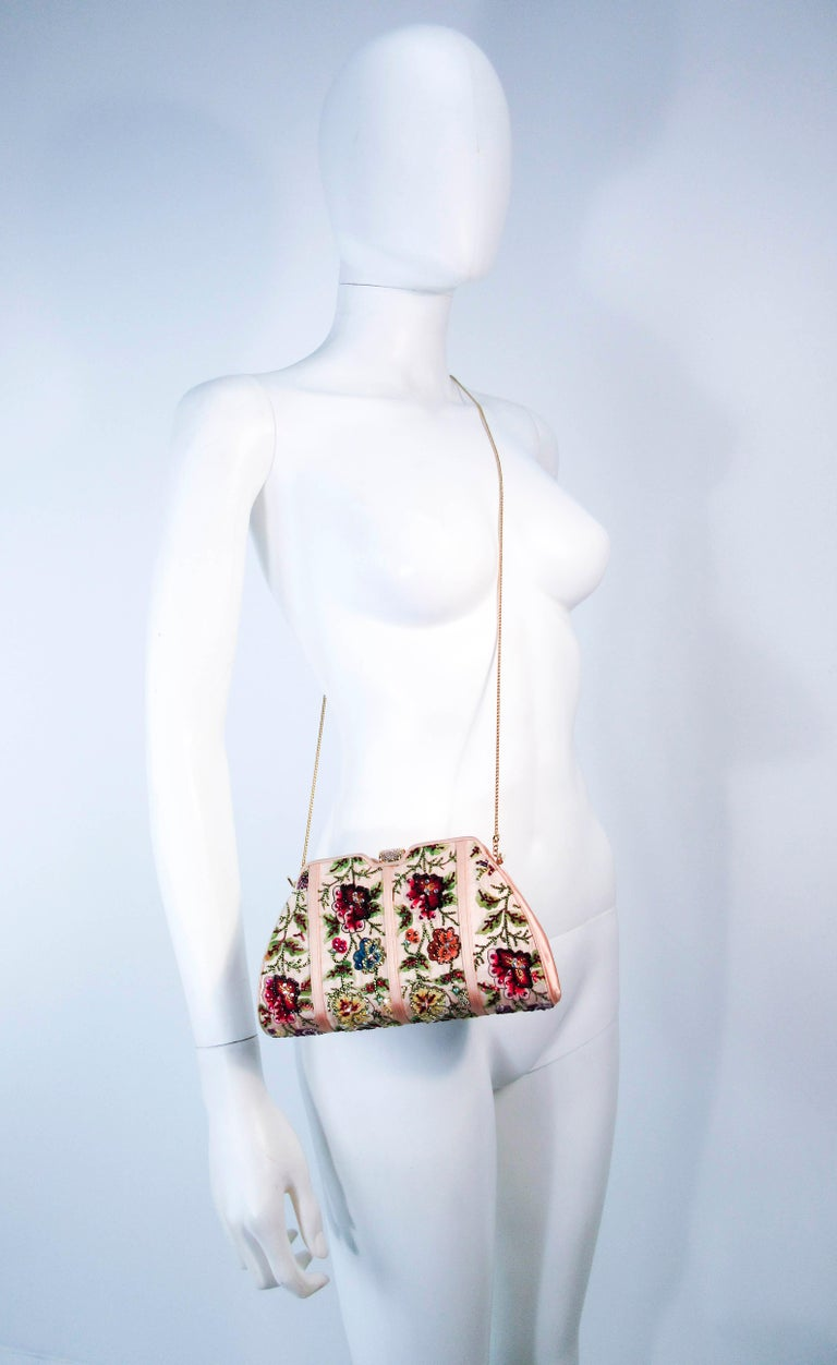 This Judith Leiber purse is composed of a peach satin with embroidery and rhinestone applique. Features a rhinestone clasp with an optional gold strap. There is an interior zipper pocket. Comes with the original comb, mirror, and coin purse. In