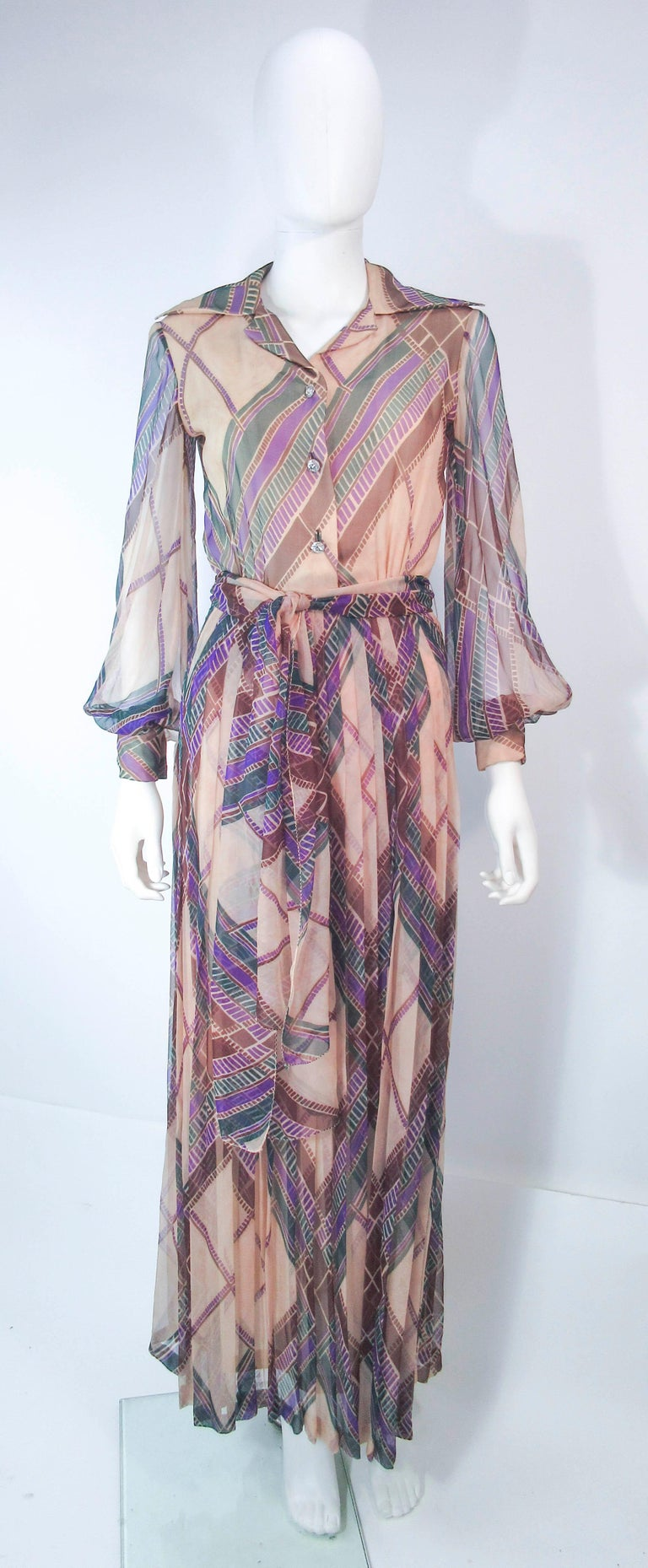 This Valentino design is composed of a beautiful abstract printed silk chiffon. Features a wonderful maxi style with center front rhinestone buttons and belt.  In excellent vintage condition, some wear (see photos).   **Please cross-reference