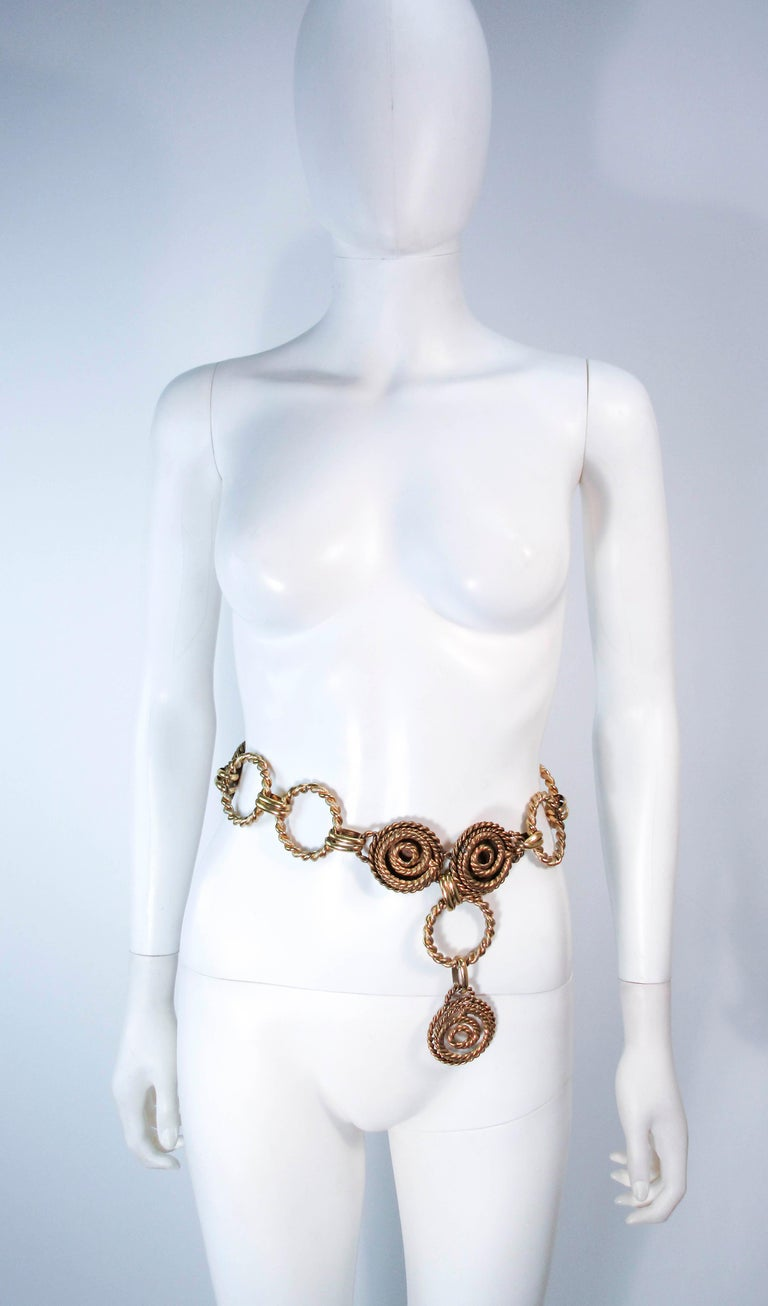 This vintage Butler & Wilson gold tone belt feature a swirl design and dangle style. This is a fantastic statement piece and excellent addition to any collectors wardrobe. In excellent vintage condition (some signs of wear due to age, see photos).