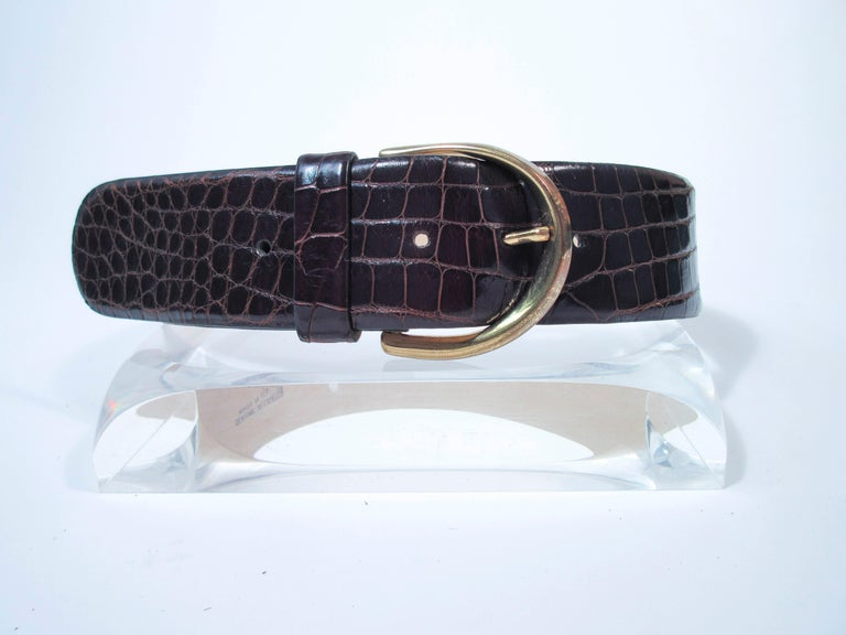 This Donna Karan belt is composed of a brown alligator. Features a classic wide style high waist style with gold tone hardware. This is a fantastic statement piece and excellent addition to any collectors wardrobe. In excellent pre-owned condition