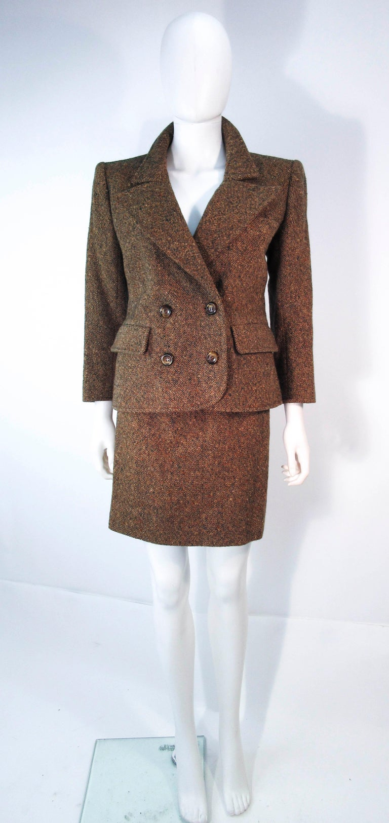 This Yves Saint Laurent suit is composed of a brown and green wool tweed. Features a beautiful classic double breasted blazer and a pencil skirt with zipper closure. In excellent vintage condition (some signs of wear due to age). Made in