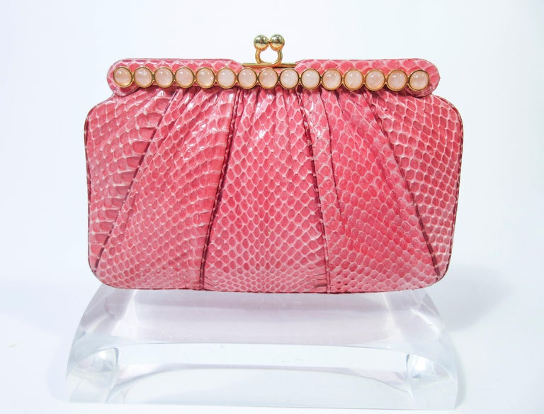 This Judith Leiber purse is composed of a pink snakeskin. Features a bar style frame with cabochon stone accents and gold hardware. There is an interior pocket and two slide pockets. In excellent 'like new' pre-owned condition (some signs of wear