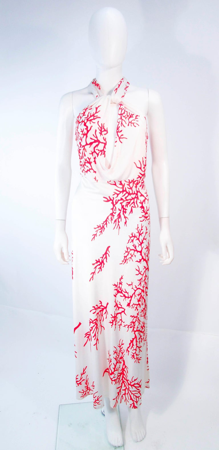 This Valentino gown is composed a white viscose with a red coral pattern. Features a lovely criss cross front with a body skimming design. In great pre-owned condition.   **Please cross-reference measurements for personal accuracy. Size in