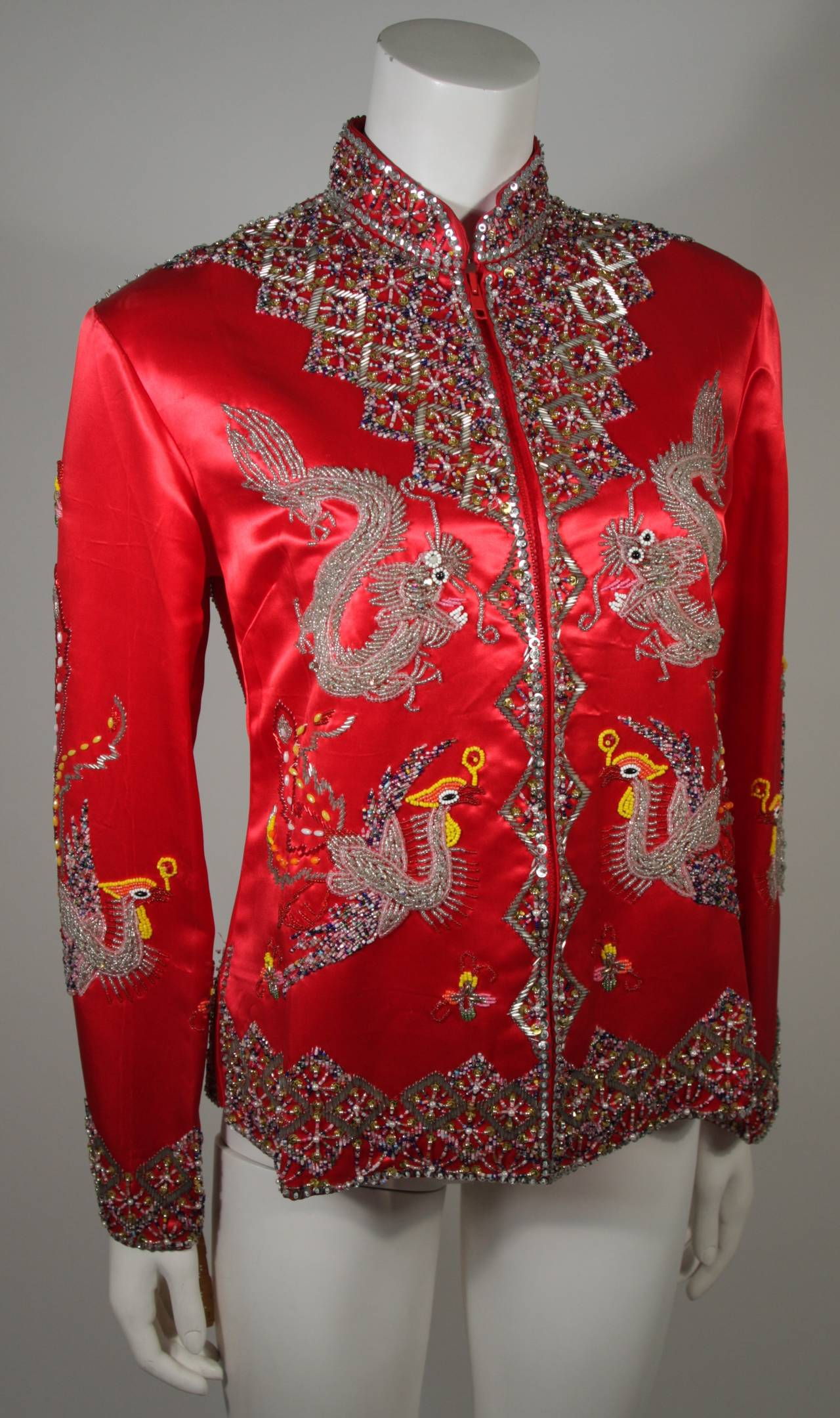 This Dynasty for Neiman Marcus jacket is composed of red embroidered silk that features hand beaded Dragon and Phoenix designs with sequin accents. There is a center front zipper. Comes with original tags and is in excellent condition.