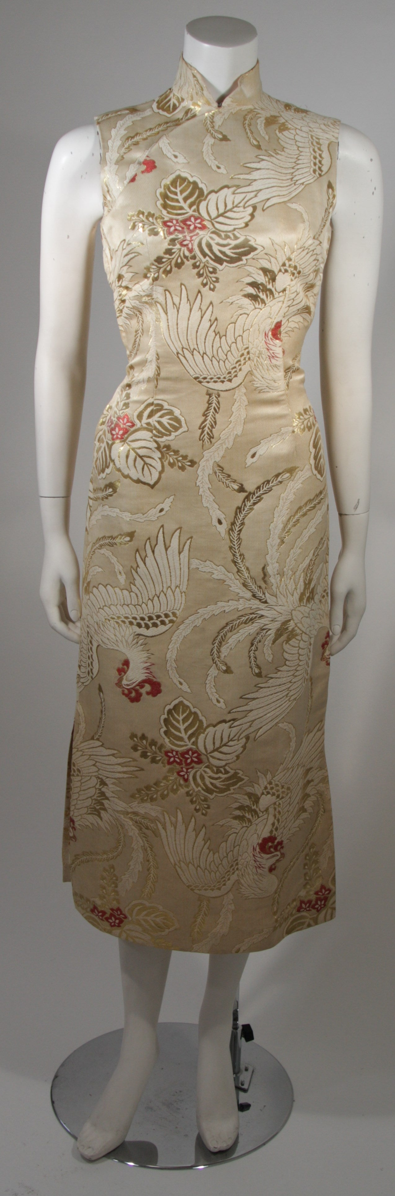 This custom made 1950's cocktail dress is composed of an ivory, cream, and gold Brocade silk with red accents. The dress features a Phoenix pattern. There is a metal side zipper closure and Mandarin neckline and side slits for ease of