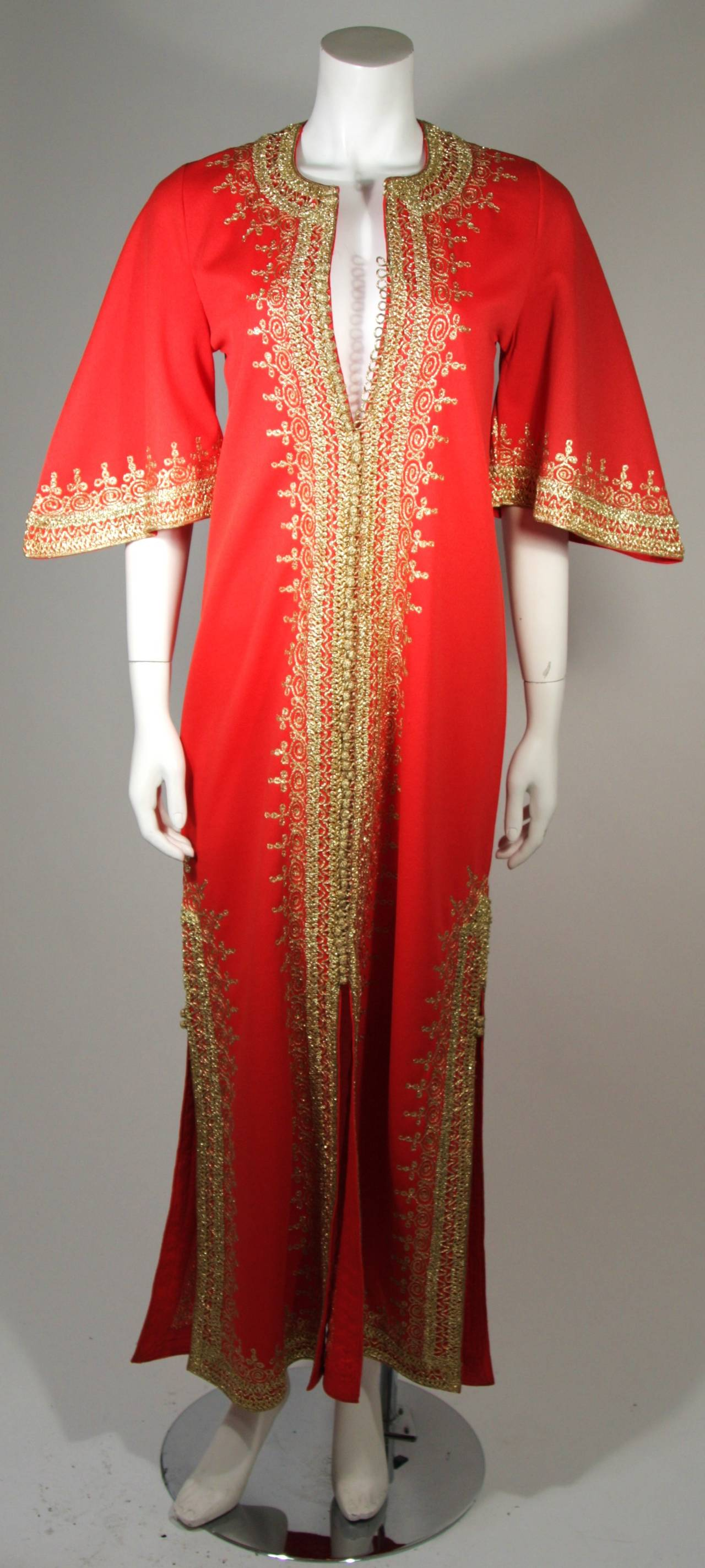 This custom vintage kaftan is composed of an orange knit and is trimmed with metallic gold. There are center front buttons, bell sleeves, and side slits. A very interesting garment in excellent condition.   **The size in the description box is an