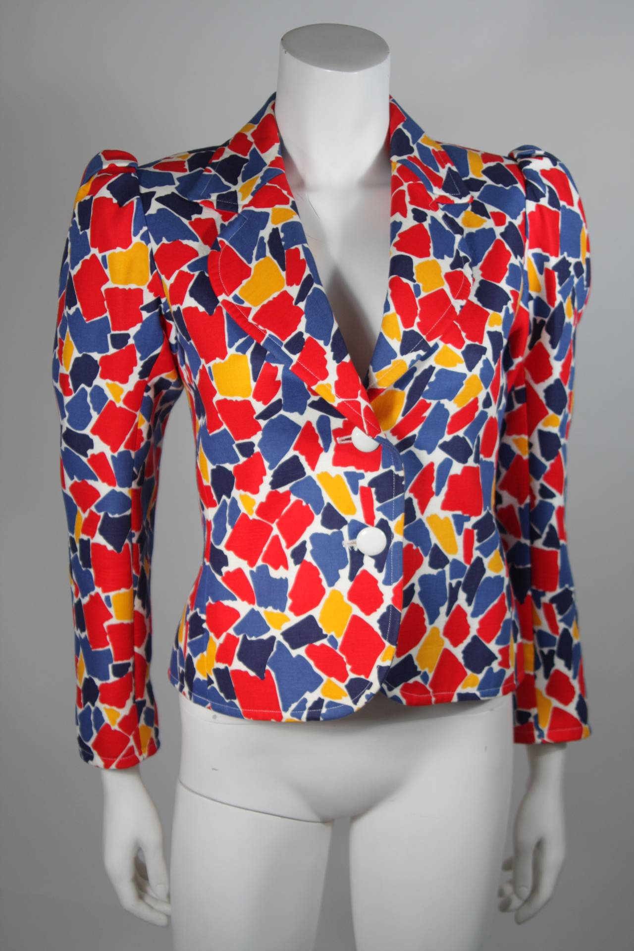 This Yves Saint Laurent jacket is composed of high contrast print in primary colors, for a pop color effect. The sleeves feature a puff style and there are center front button closures. In excellent condition. Made in France. 