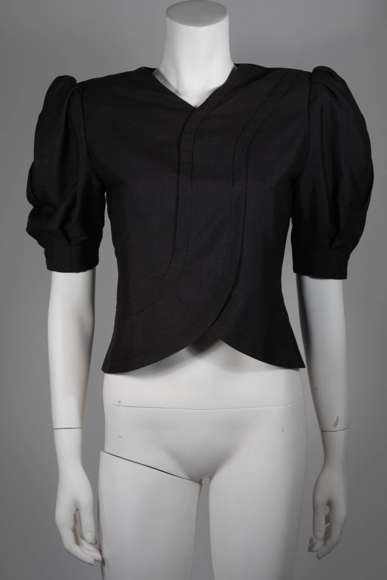 This Galanos blouse is composed of a raw black silk. The center front seam line designs are accented by the puff style sleeves. There is a center back zipper closure. In excellent condition.   **Please cross-reference measurements for personal