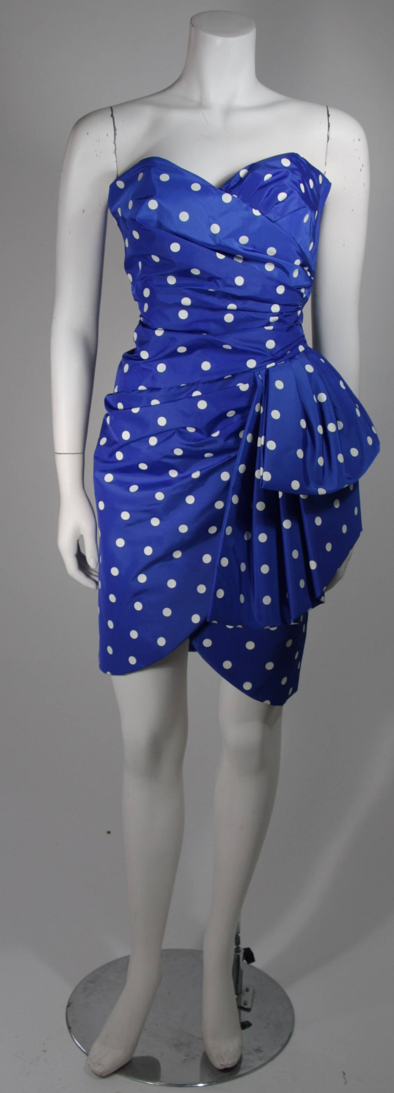 This Victor Costa cocktail dress is composed of a royal blue and white polka fabric. The gathered design is accented by a large side draping bow at the hip. There is a side zipper closure. In excellent condition. Made in United States Of America.