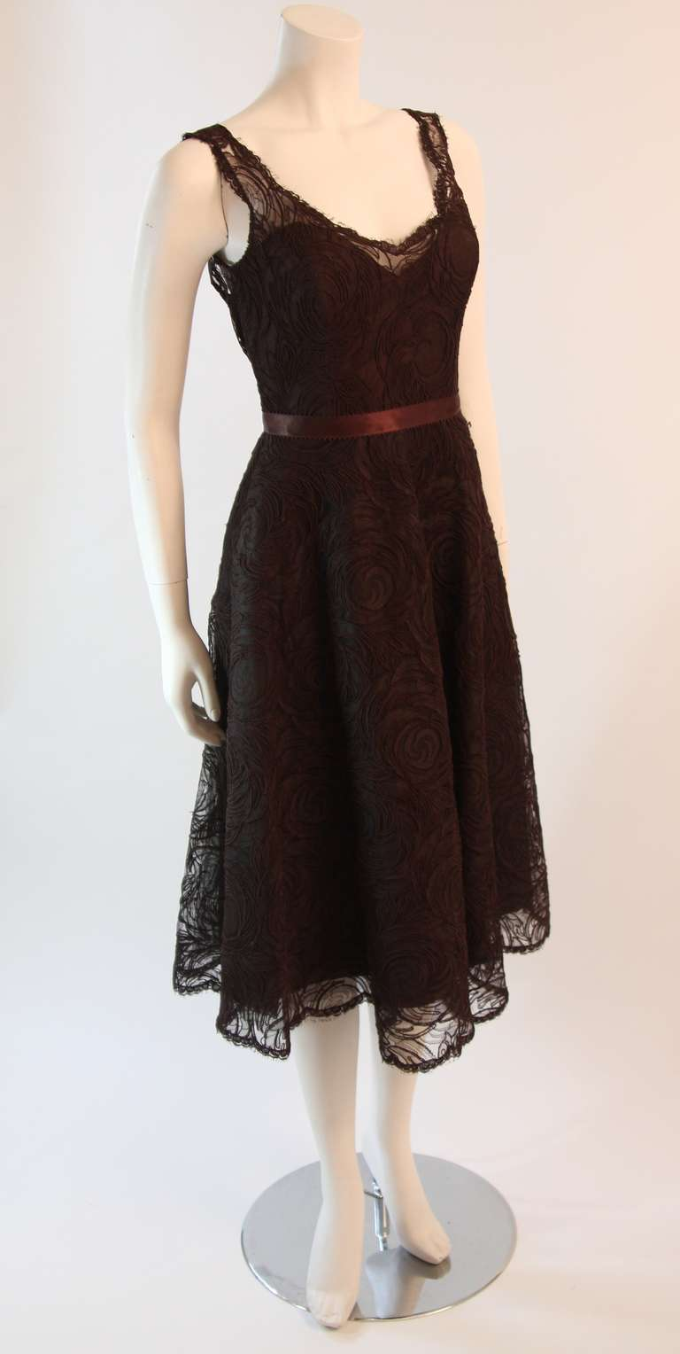 This is a stellar Monique Lhuillier cocktail dress. It is a wonderful brown lace, features a brown bow, and scalloped lace design. Zipper detail at the center back.