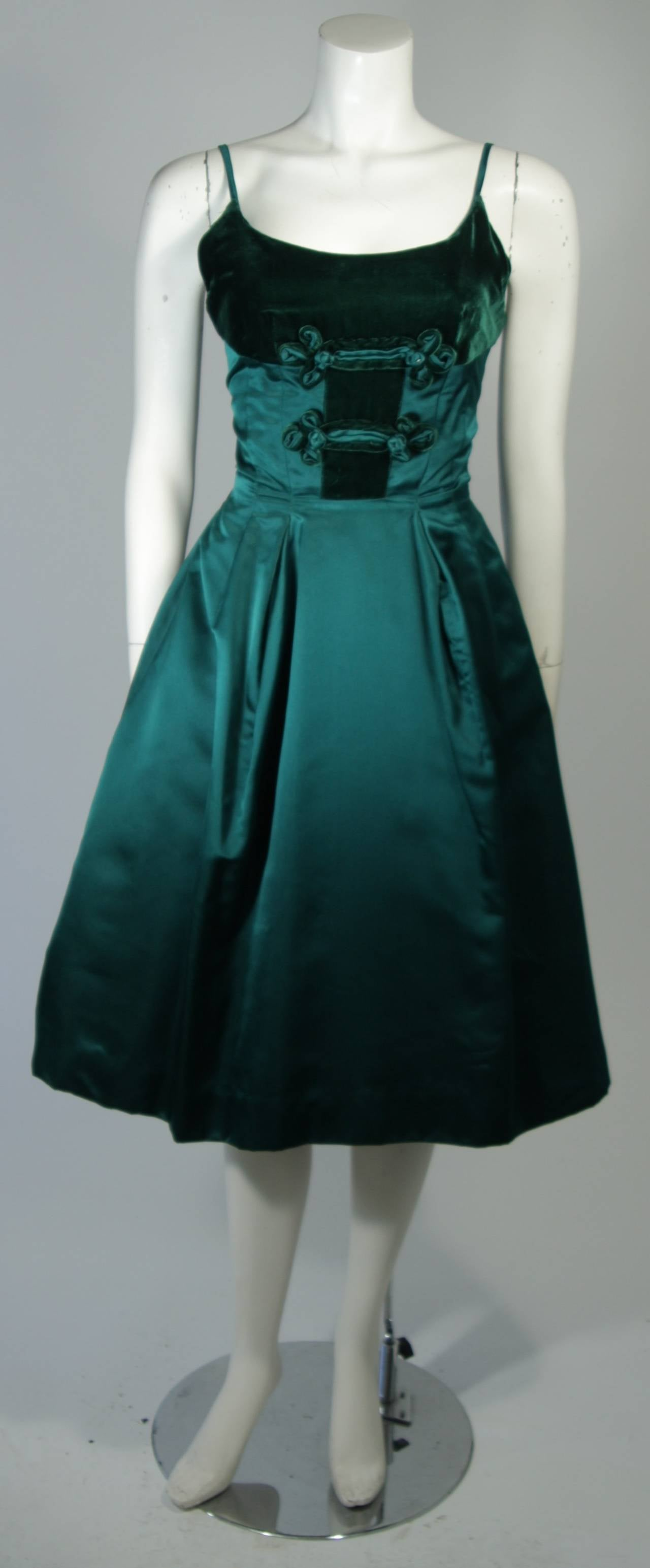 This Oleg Cassini cocktail dress is fashioned from a superb green velvet and satin combination which features a bust applique. There are spaghetti straps, full skirt, and a center back zipper. In excellent vintage condition.  