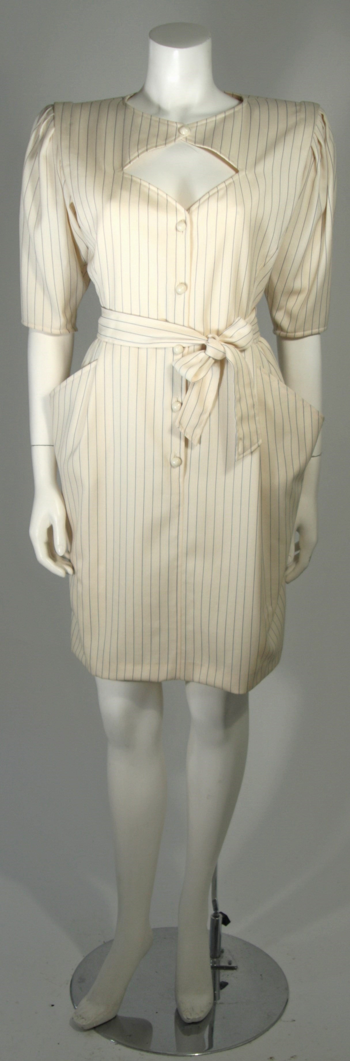This Ungaro cocktail dress is composed of a cream pin stripe wool. The dress features center front buttons and a belt. In excellent condition. Made in Italy.